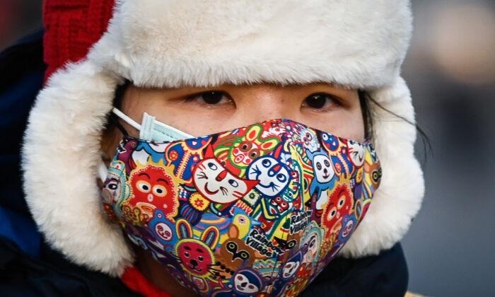 Mujer con una mascarilla en una calle de Beijing, China, el 10 de diciembre de 2020. (WANG ZHAO/AFP vía Getty Images)