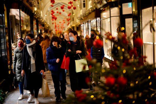Los compradores, algunos con una mascarilla debido a la pandemia de COVID-19, miran los escaparates de las tiendas dentro de un Burlington Arcade con temática navideña en Londres, Inglaterra, el 19 de diciembre de 2020. ( Foto de TOLGA AKMEN / AFP a través de Getty Images)