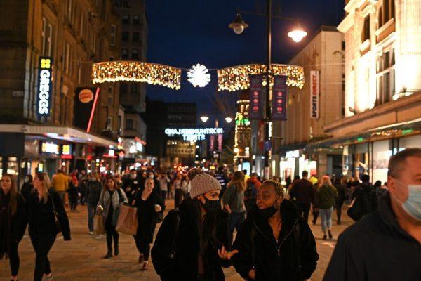Los peatones con mascarillas para combatir la propagación de la pandemia del covid-19, caminan por el centro de Newcastle-upon-Tyne, en el noreste de Inglaterra, el 19 de diciembre de 2020. (Foto de OLI SCARFF / AFP a través de Getty Images)