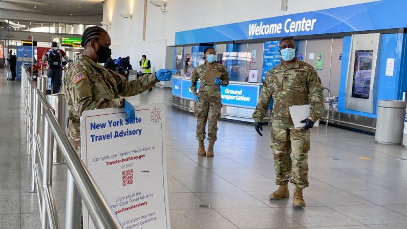 El personal militar pasa información a los viajeros cuando llegan a la terminal 4 del aeropuerto internacional JFK de Nueva York (EE.UU.) el 22 de diciembre de 2020. (Foto de KENA BETANCUR / AFP a través de Getty Images)