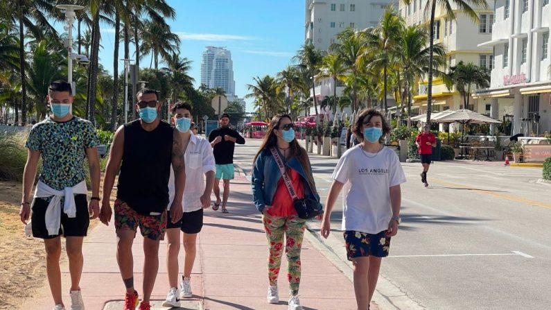 Personas con mascarillas caminan en Miami Beach, Florida (EE.UU.) el 22 de diciembre de 2020 en medio de la pandemia de covid-19. (Foto de DANIEL SLIM / AFP a través de Getty Images)