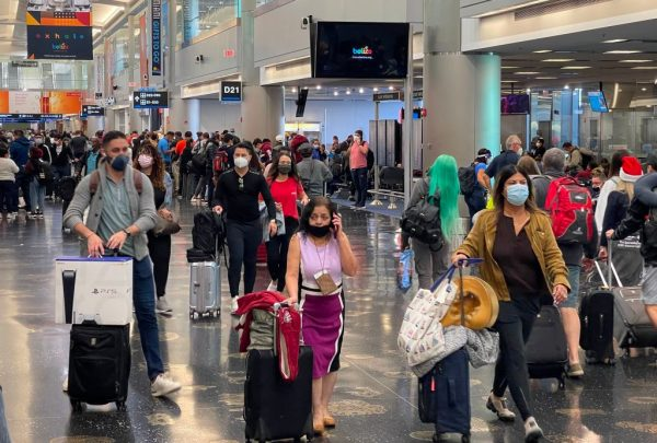 Los viajeros usan mascarillas en el Aeropuerto Internacional de Miami el 24 de diciembre de 2020, en medio de la pandemia de covid-19. (Foto de DANIEL SLIM / AFP a través de Getty Images)