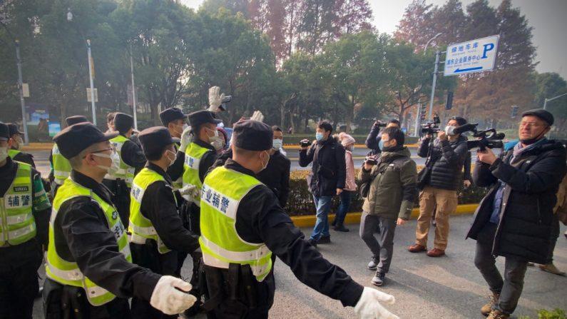 Policía intenta impedir que periodistas graben imágenes fuera del Tribunal Popular del Nuevo Distrito de Pudong en Shanghai, el 28 de diciembre de 2020. (Leo Ramirez/AFP a través de Getty Images)