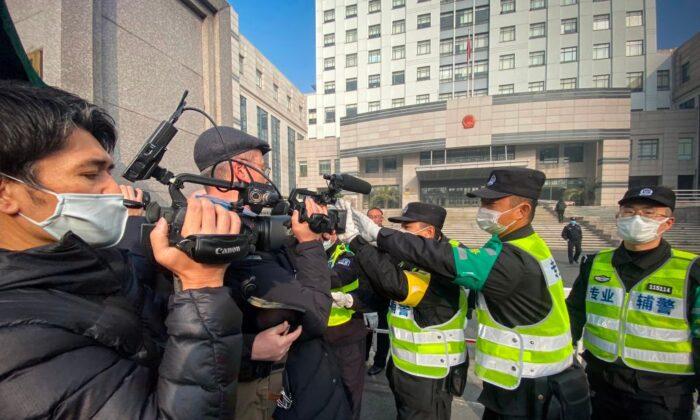 La policía trata de impedir que los periodistas graben imágenes fuera del Tribunal Popular del Nuevo Distrito de Pudong en Shanghai, China, el 28 de diciembre de 2020. (Leo Ramirez/AFP vía Getty Images)