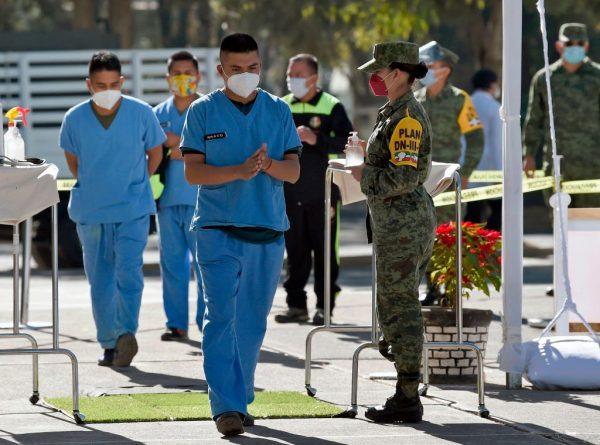 Llega personal médico de diferentes instituciones para vacunarse con la vacuna Pfizer / BioNTech contra el COVID-19, al Campo Militar Número 1A de la Ciudad de México (México) el 28 de diciembre de 2020. (Foto de ALFREDO ESTRELLA / AFP vía Getty Images)