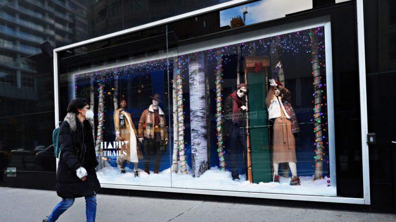 Una persona con una mascarilla camina junto a una ventana de vacaciones en la calle 59 de Bloomingdale el 8 de diciembre de 2020 en la ciudad de Nueva York (EE.UU.). (Foto de Cindy Ord / Getty Images)