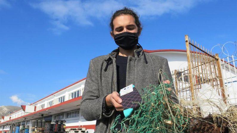 Lefteris Arapakis, ganador del premio de la ONU Jóvenes Campeones de la Tierra, muestra los calcetines en los que se transforman los plásticos, gracias a la colaboración de empresas como la española Ecoalf que fabrican productos sostenibles, en Atenas (Grecia). (Alberto Borreguero/EFE)