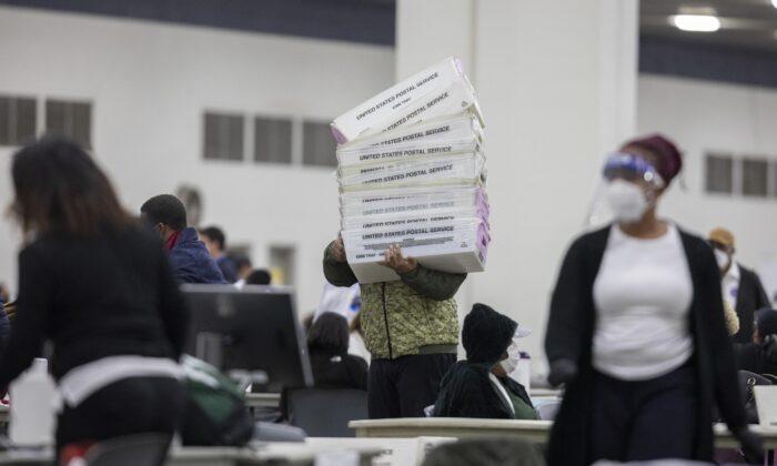Trabajador del Departamento de Elecciones de Detroit lleva las cajas vacías que se utilizan para organizar los votos de los ausentes en la Junta Central de Conteo en el Centro TCF en Detroit, Michigan, el 4 de noviembre de 2020. (Elaine Cromie/Getty Images)