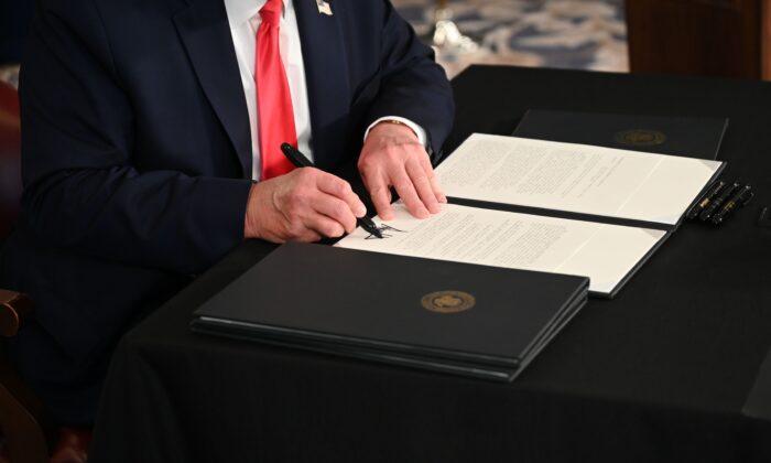El presidente Donald Trump firma una orden ejecutiva en Bedminster, Nueva Jersey, el 8 de agosto de 2020. (Jim Watson/AFP a través de Getty Images)