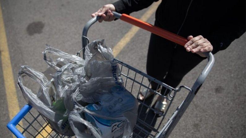 Un estudiante de secundaria es visto saliendo de una tienda de comestibles después de abastecerse de víveres, el 13 de marzo de 2020 en Englewood, Ohio. (Brad Lee/AFP/AFP vía Getty Images)