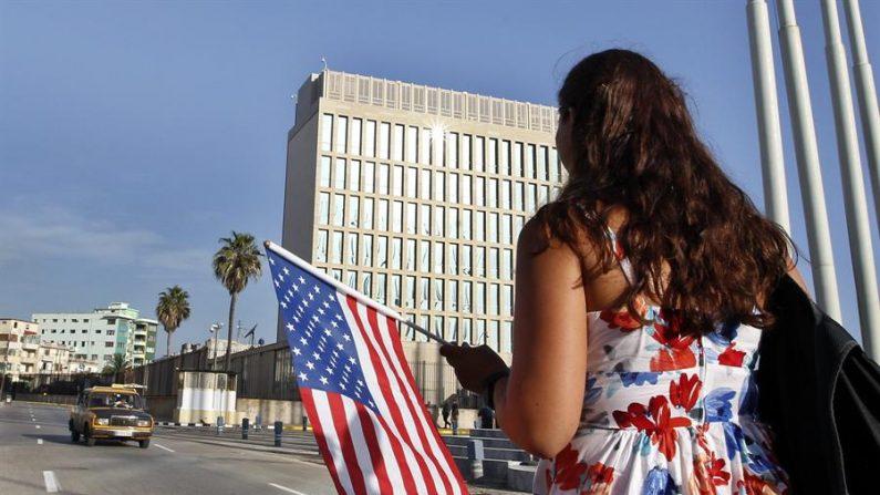 Una mujer camina con una bandera de EE. UU. frente a la embajada de ese país en La Habana (Cuba). EFE/Ernesto Mastrascusa/Archivo
