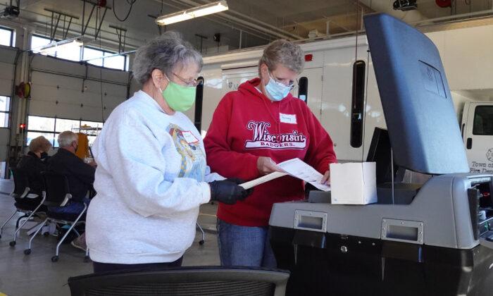 Los funcionarios electorales cuentan las boletas en ausencia en un centro de votación ubicado en la estación de bomberos de la ciudad de Beloit, cerca de Beloit, Wisc., el 3 de noviembre de 2020. (Scott Olson/Getty Images)
