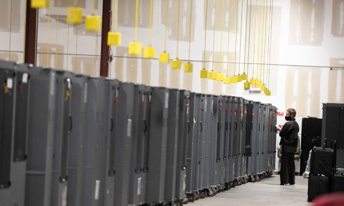 Un observador electoral del Partido Republicano de Georgia observa los transportadores de máquinas de votación que se almacenan en el Centro de Preparación para las Elecciones del Condado de Fulton en Atlanta, Georgia, el 4 de noviembre de 2020. (Jessica McGowan/Getty Images)
