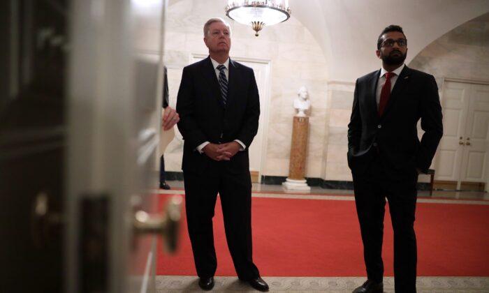 Kash Patel, a la izquierda, entonces director de contraterrorismo del Consejo de Seguridad Nacional, apoya al senador Lindsey Graham (R-S.C.) en la Casa Blanca en Washington el 29 de octubre de 2019. (Alex Wong/Getty Images)