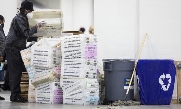 Un trabajador del Departamento de Elecciones de Detroit ayuda a apilar las cajas vacías utilizadas para organizar los votos en ausencia en la Junta Central de Conteo en el Centro TCF en Detroit, Mich. el 4 de noviembre de 2020. (Elaine Cromie/Getty Images)
