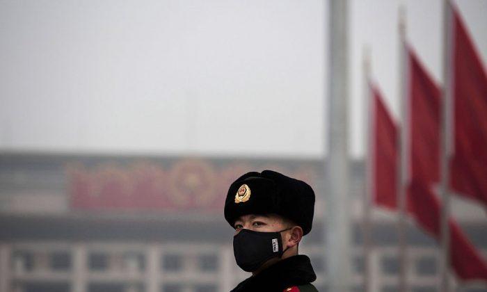 Un policía paramilitar chino usa una mascarilla para protegerse de la contaminación en la Plaza de Tiananmen el 9 de diciembre de 2015 en Beijing, China. (Kevin Frayer/Getty Images)