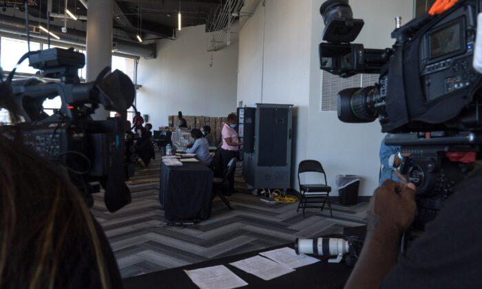 Equipos de medios filman mientras los trabajadores electorales procesan las papeletas de voto en ausencia, en el State Farm Arena, en Atlanta, Georgia, el 2 de noviembre de 2020. (Megan Varner/Getty Images)