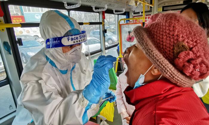 Un trabajador de la salud toma un hisopo de un residente para hacer la prueba de COVID-19 en Dalian, China, el 23 de diciembre de 2020. (STR/AFP vía Getty Images)