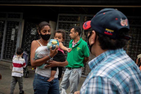Fotografía fechada el 6 de enero de 2021, que muestra a una mujer mientras recibe un donativo, en Caracas (Venezuela). EFE/ Rayner Peña R