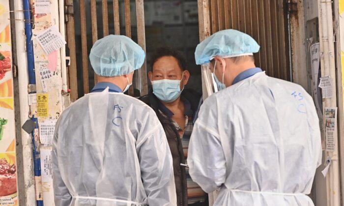 Un residente en el área restringida del barrio Jordania, en Hong Kong, pregunta a los trabajadores médicos sobre los suministros de alimentos, el 24 de enero de 2021. (Adrian Yu/Epoch Times)