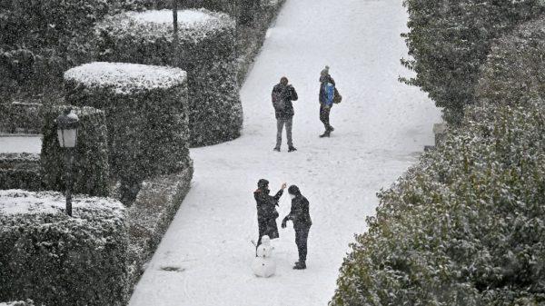 La gente hace un muñeco de nieve en los jardines de Sabatini fuera del Palacio Real de Madrid, España, el 8 de enero de 2021 cuando cae una nevada. (Foto de GABRIEL BOUYS / AFP a través de Getty Images)