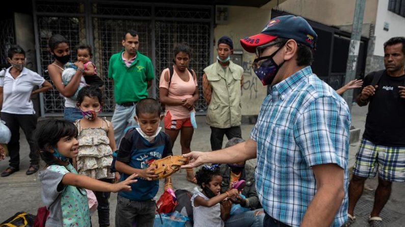 Fotografía fechada el 6 de enero de 2021, que muestra a Manuel Santos (i) mientras entrega algunos donativos a niños, en Caracas (Venezuela). EFE/ Rayner Peña R