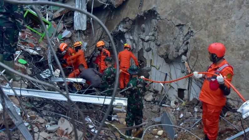 Los equipos de rescate buscan sobrevivientes en un edificio derrumbado en Mamuju el 15 de enero de 2021, luego de que un terremoto de magnitud 6.2 sacudiera la isla indonesia de Sulawesi. (Foto de Firdaus / AFP a través de Getty Images)