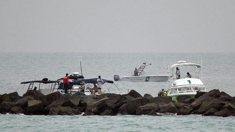 Los equipos de rescate de Miami Dade trabajan en el lugar de un accidente frente al embarcadero en Government Cut en el sur de Miami Beach, Florida, el 19 de diciembre de 2005. (Foto de archivo de ROBERTO SCHMIDT / AFP a través de Getty Images)