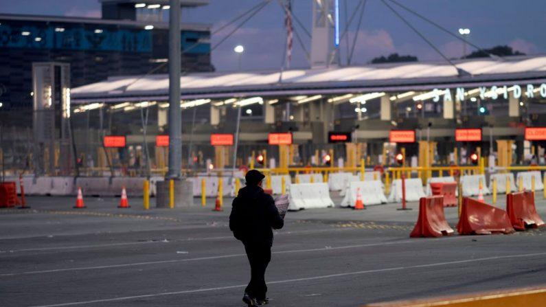 Un vendedor ambulante camina cerca de carriles cerrados en el puerto de entrada de San Ysidro en la frontera entre México y Estados Unidos, visto desde Tijuana, estado de Baja California, México, el 21 de marzo de 2020. (Foto de GUILLERMO ARIAS / AFP vía Getty Images)
