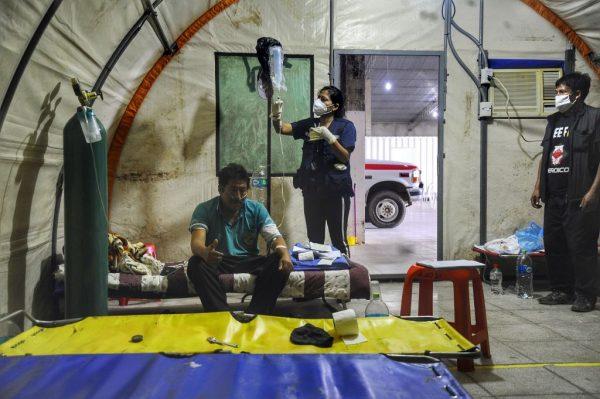 """Médicos voluntarios miembros de la organización """"Ángeles contra el Covid"""", asisten a un paciente con COVID-19 en su tienda de campaña en Santa Cruz, Bolivia, el 13 de julio de 2020. (Foto de ENRIQUE CANEDO / AFP a través de Getty Images)"""