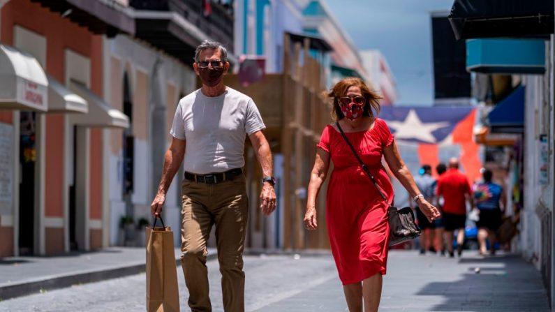 Turistas con mascarillas caminan por una calle del Viejo San Juan, Puerto Rico el 20 de julio de 2020. (Ricardo Arduengo / AFP vía Getty Images)