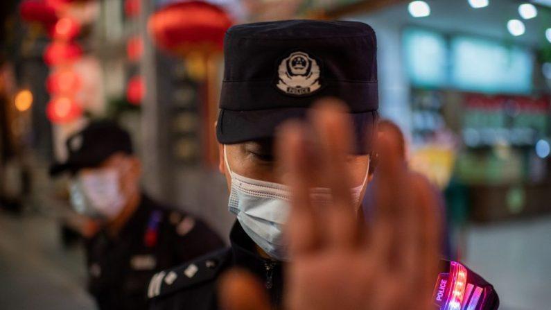 Un oficial de policía que usa una mascarilla como medida preventiva contra el Covid-19 (nuevo coronavirus) intenta detener a un reportero gráfico para que tome fotografías en una calle fuera de un centro comercial en Beijing el 13 de octubre de 2020 (Foto por NICOLAS ASFOURI / AFP) (Foto de NICOLAS ASFOURI / AFP a través de Getty Images)