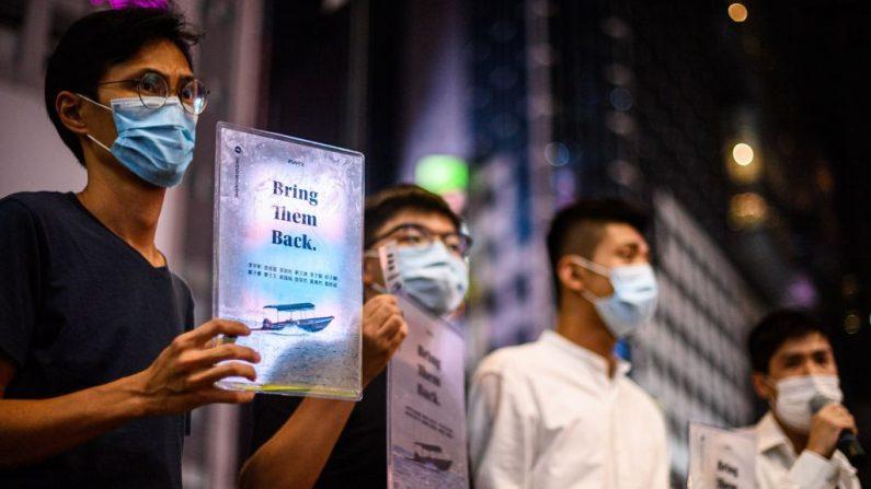Los activistas prodemocracia de Hong Kong, Eddie Chu, Joshua Wong, Owen Chow y Lester Shum sostienen carteles el 20 de octubre de 2020, en apoyo de los 12 activistas locales detenidos en China continental, después de que la guardia costera interceptara un barco que los transportaba a Taiwán a fines de agosto. (Foto de Anthony Wallace/AFP vía Getty Images)
