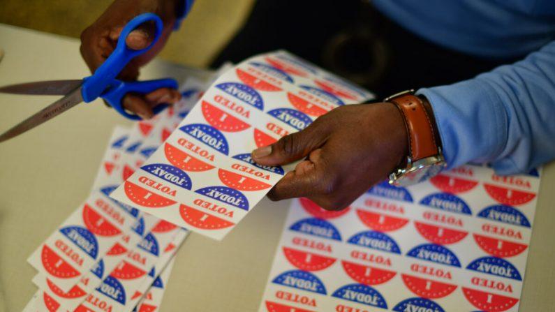 """Un voluntario recorta las calcomanías de """"Yo voté hoy"""" para los votantes que hacen fila frente a un centro de votación en Filadelfia, Pa., el 27 de octubre de 2020. (Mark Makela/Getty Images)"""
