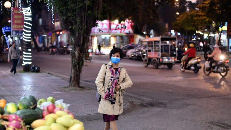 Una mujer que llevaba una mascarilla camina por una calle de Hanói (Vietnam) el 1 de diciembre de 2020, un día después de que Vietnam reportara su primer caso de transmisión local de covid-19 en casi tres meses. (Foto de MANAN VATSYAYANA / AFP a través de Getty Images)