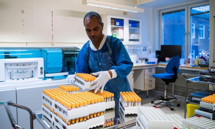 Un miembro del personal del laboratorio del hospital de Karolinska opera una máquina utilizada en el proceso de pruebas de PCR para personas que piensan que pueden estar sufriendo de COVID-19, en Solna cerca de Estocolmo, Suecia, el 7 de diciembre de 2020. (Jonathan Nackstrand/AFP vía Getty Images)