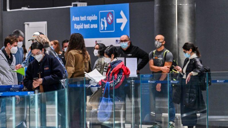 Los pasajeros que acaban de aterrizar en un vuelo de Alitalia esperan en la fila mientras se preparan para someterse a una prueba rápida con hisopo de antígeno para COVID-19 el 9 de diciembre de 2020 en un Área de Prueba Rápida establecida en el aeropuerto de Fiumicino de Roma, Italia. (Foto de ANDREAS SOLARO / AFP a través de Getty Images)