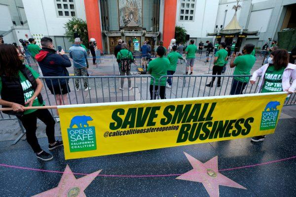Miembros de los propietarios de pequeños negocios practican el distanciamiento social frente al Teatro Chino TCL antes de la protesta 'Save Small Business' en Los Ángeles, California, el 12 de diciembre de 2020. (Foto de RINGO CHIU / AFP vía Imágenes falsas)