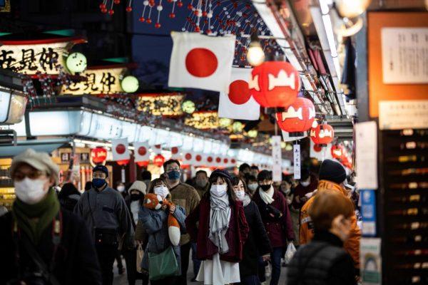 Personas con mascarillas caminan por la calle comercial del templo Sensoji en el distrito de Asakusa de Tokio, Japón, el 2 de enero de 2021. (Foto de BEHROUZ MEHRI / AFP a través de Getty Images)