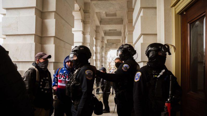 La policía del Capitolio, con equipo antidisturbios, se enfrenta a un grupo de manifestantes después de sacarlos del edificio el 6 de enero de 2021 en Washington, DC. (Jon Cherry/Getty Images)
