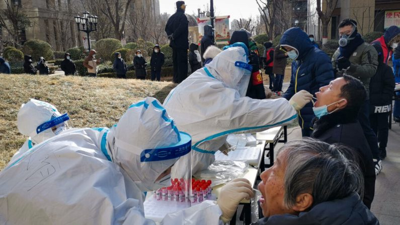 Trabajadores médicos toman muestras de hisopado a residentes en Shijiazhuang, provincia de Hebei, al norte de China, el 6 de enero de 2021. (STR/CNS/AFP a través de Getty Images)
