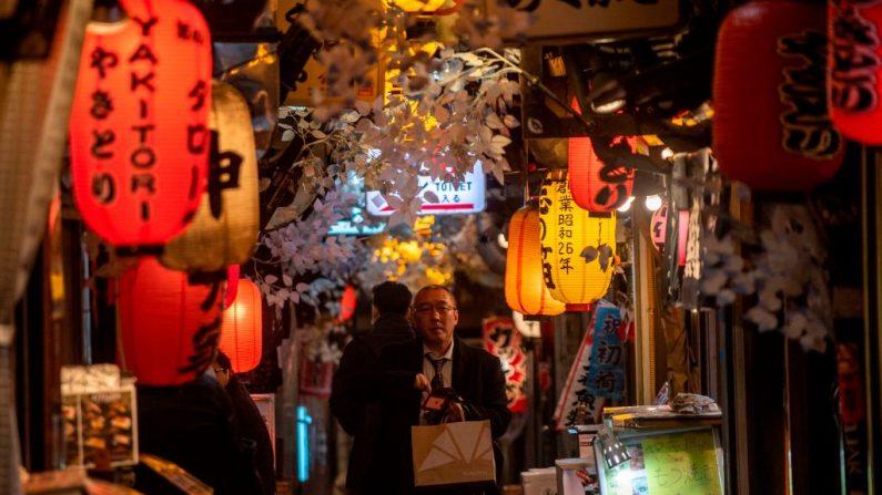 Un hombre pasa junto a los restaurantes en el callejón Omoide Yokocho en el distrito de Shinjuku en Tokio (Japón) el 7 de enero de 2021. (Foto de PHILIP FONG / AFP a través de Getty Images)