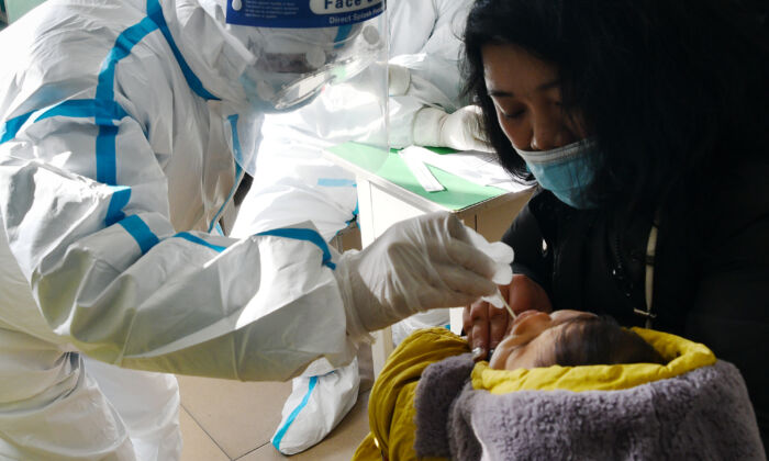 Un trabajador médico toma una muestra de hisopo de un bebé para la prueba de COVID-19 en Shijiazhuang, en la provincia de Hebei, en el norte de China, el 7 de enero de 2021 (STR / CNS / AFP a través de Getty Images).