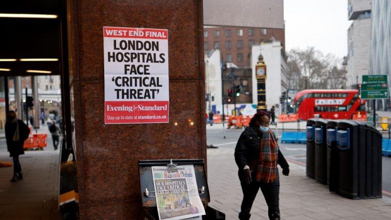 Una mujer con una mascarilla pasa frente a un puesto de los periódicos Evening Standard en el centro de Londres, el 8 de enero de 2021, cuando Inglaterra ingresó a un tercer bloqueo debido al covid-19. (Foto de TOLGA AKMEN / AFP a través de Getty Images)