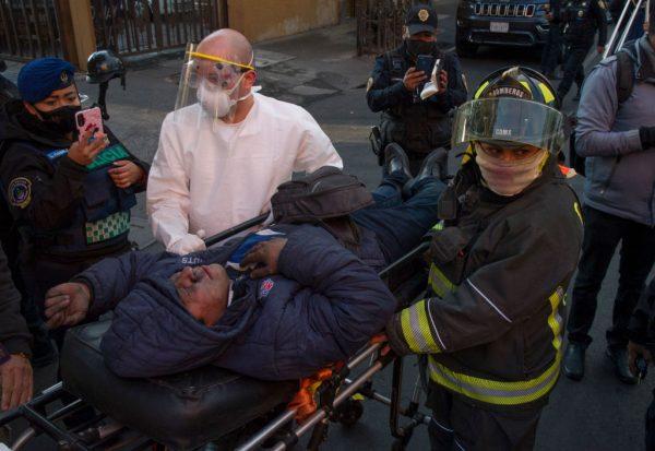 Un hombre que sufre inhalación de humo es transportado en camilla por personal médico luego de ser rescatado de un incendio en la subestación eléctrica de la sede del Metro de la Ciudad de México en el centro histórico de la capital mexicana el 9 de enero de 2021. (Foto de CLAUDIO CRUZ / AFP a través de Getty Images)
