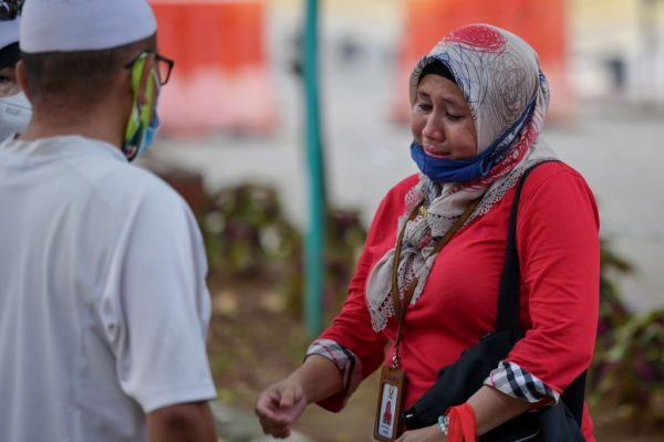 Familiares de una de las 62 personas a bordo del vuelo SJ182 de Sriwijaya Air, que se estrelló poco después del despegue el 9 de enero, reaccionan mientras realizan una prueba de ADN en un hospital policial en Yakarta (Indonesia) el 12 de enero de 2021. (Foto de BAY ISMOYO / AFP a través de Getty Images)
