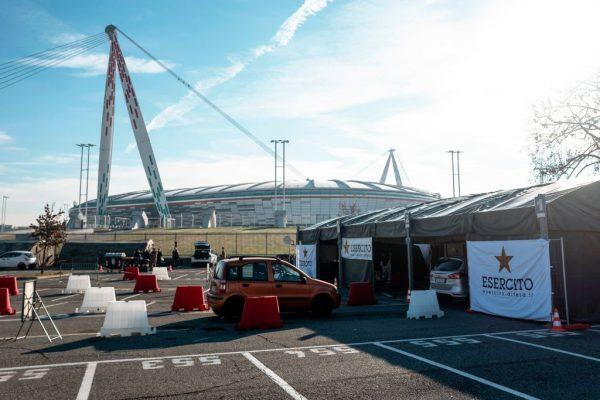 Una vista general muestra el 12 de enero de 2021 un automóvil haciendo cola para pasar por un centro de pruebas de hisopos de COVID-19 instalado por el ejército italiano en el estacionamiento del estadio de la Juventus en Turín. (Foto de MARCO BERTORELLO / AFP vía Getty Images)
