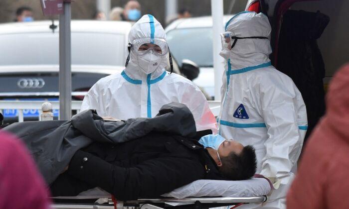 Los trabajadores médicos llevan a un paciente a la clínica de fiebre en un hospital en Beijing, el 13 de enero de 2021. (GREG BAKER/AFP a través de Getty Images)