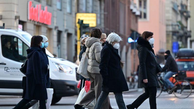 Milaneses con mascarillas caminan por un paso de peatones en el área comercial de Corso Buenos Aires en el centro de Milán, Italia, el 13 de enero de 2021. (Foto de MIGUEL MEDINA / AFP vía Getty Images)