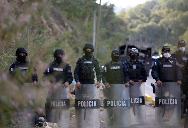 Fuerzas de seguridad montan guardia en El Florido, en el departamento hondureño de Copán, al otro lado de la frontera con Guatemala, mientras los migrantes que desean llegar a Estados Unidos comienzan a reunirse con la esperanza de cruzar la frontera para la primera caravana del año, el 15 de enero. 2021. (Foto de Johan Ordonez / AFP a través de Getty Images)